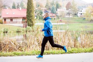 Athlete at the lake running against colorful autumn nature