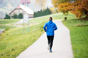 Athlete at the lake running on concrete path, rear view.
