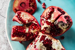 cut ripe red pomegranate on a plate on a stone table. fruit of h