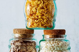 Variety of cold quick breakfast cereals in glass jars , healthy