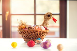 Crocheted Easter eggs and straw hen in wicker basket