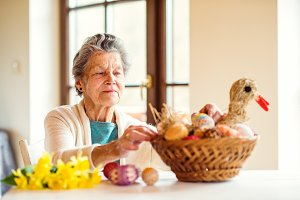 Senior woman arranging basket with Easter eggs and daffodils
