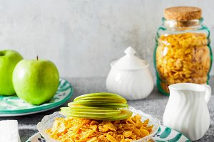 Cornflake cereals in a bowl with milk and a green apple , quick