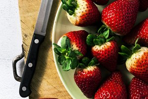 a pile of fresh juicy ripe strawberries on a cutting board and a