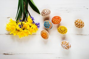 Colorful crocheted Easter eggs and daffodil bouquet, wooden back