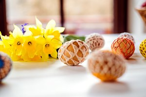Colorful crocheted Easter eggs and daffodil laid on table