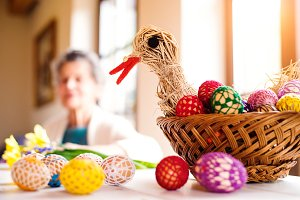 Basket with Easter eggs and hen in senior woman house