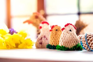 Colorful crocheted Easter chickens and daffodil laid on table