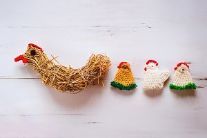 Three crocheted Easter chickens and straw hen,white wooden backg