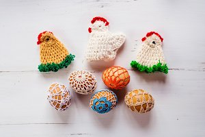Colorful crocheted Easter chickens and eggs against wooden backg