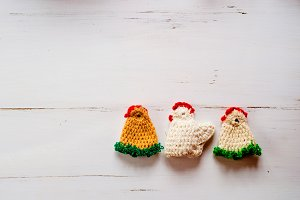 Three colorful crocheted Easter chickens against white wooden ba