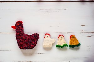 Three crocheted Easter chickens and knitted hen,white wooden bac