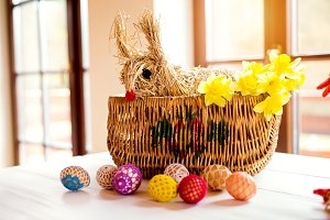 Wicker basket, straw Easter bunny and daffodils, crocheted eggs