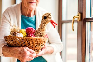 Woman holding basket with Easter eggs and straw hen