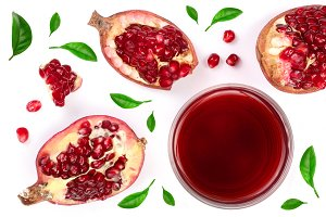 A glass of pomegranate juice with fresh pomegranate fruits decorated with leaves isolated on white background. Top view.