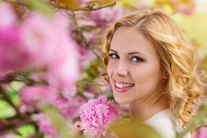 Blond woman, curly hair against pink tree in blossoom