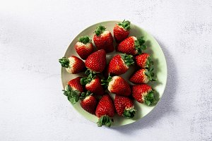 a pile of fresh juicy ripe strawberries on the plate