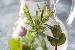 Glass jar of water with herbs