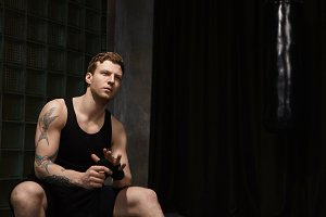 Indoor shot of thoughtful attractive young European man wearing sleeveless shirt and shorts wrapping boxing bandages, sitting against black curtain background with copyspace for your information