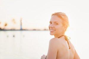 Attractive woman in bikini at the shore near lighthouse