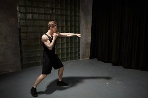 Picture of stylish fit Caucasian guy with muscular tattooed shoulders boxing in empty room reaching out one hand, mastering punches while preparing for fight. People, healthy lifestyle and sports