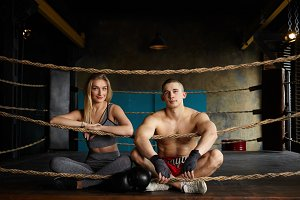 Picture of attractive young athletic couple man and woman sitting cross legged on floor inside boxing ring after intensive workout, having happy confident looks, wearing stylish sports clothes