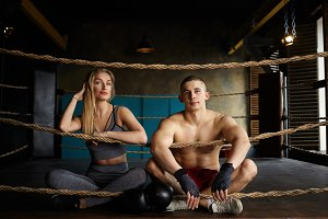 Horizontal shot of fashionable handsome young male boxer with muscular naked torso wearing white sneakers and bandages sitting next to beautiful blonde female, looking and smiling at camera