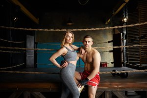 Portrait of stylish young male and female with slim muscular bodies posing in gym, sitting outside boxing ring, embracing, choosing healthy active lifestyle. Martial arts, sports and fitness concept