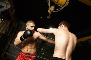Freeze action shot of male boxer with perfect abs and sweaty muscular torso wearing red trousers and black leather gloves fighting against unrecognizable opponent, mastering punching techniques