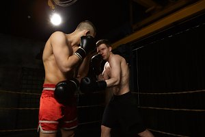 Competition, rivalry, people and sports concept. Serious self confident young Caucasian man with tattoos and muscular arms fighting against unrecognizable male in red trousers. Two fighters boxing