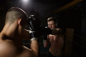 Portrait of handsome young man with muscular naked torso reaching out one hand in gloves, mastering punches with his coach in gym. Martial arts, MMA, boxing, sparring and competition concept