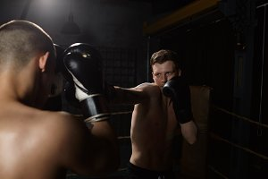 Sports, strength, determination, endurance, competition and championship concept. Portrait of determined furious young European man boxer in gloves punching his unrecognizable opponent in face