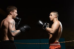 People, sports, MMA and martial arts concept. Sideways portrait of two young athletic Caucasian men with naked sweaty muscular torso fighting, standing opposite each other inside boxing ring