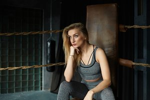 Horizontal indoor shot of attractive serious young blonde slim woman of European appearance sitting inside boxing ring with elbows on her knees, having break after training, looking ahead of her