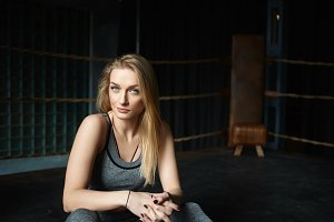 Healthy active lifestyle, fitness, endurance and strength concept. Portrait of cute blonde sportswoman in gray leggings and bra, having rest between training boxing session, sitting inside boxing ring