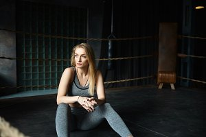 Gorgeous beautiful young woman dressed in gray sportswear having break during physical exercises in gym in the morning before work. Blonde fit girl with slim perfect body sitting on floor and resting