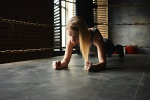 Beautiful young blonde woman in sports clothes exercising indoors, doing elbow plank inside boxing ring, testing endurance, having concentrated focused look. Athletic sporty girl training in gym