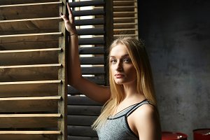 Portrait of beautiful blonde female with perfect slim body posing indoors in sportswear holding hand on window casement and looking at camera with serious confident expression on her pretty face