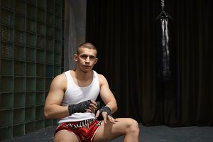 Cropped shot of serious attractive young European male kickboxer in stylish sports outfit wrapping black elastic bandages, getting ready for training, punching bag hanging out in background