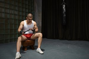 Candid shot of shaved concentrated young sportsman with strong muscular arms sitting on leather chair in gym, wrapping bandages, wearing white running shoes, sleeveless shirt and red trousers