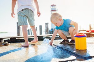 Two boys playing on the pier, lighthouse, sunny summer