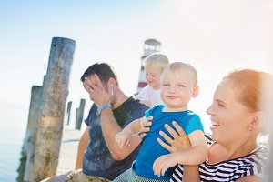 Family sitting on the pier, lighthouse, sunny summer day