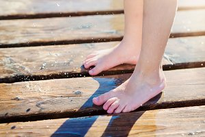 Detail of childs wet feet on pier, sunny summer day