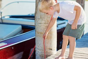 Boy on the pier with motorboat, sunny summer