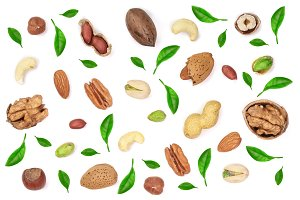 mix of different nuts decorated with green leaves isolated on white background, Flat lay pattern, Top view