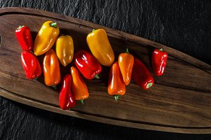 banner of colored sweet pepper on black slate. background of foo