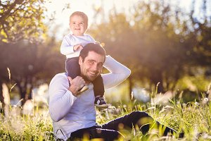 Father carrying son on shoulders, sitting on the grass