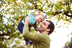 Father holding little son, throwing him in the air