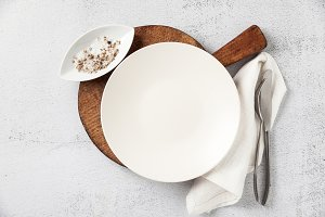 empty plate and cutlery on a wooden cutting board. a fork, a kni