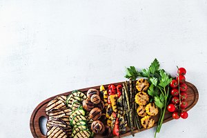 grilled vegetables on a wooden tray on a white stone table. copy
